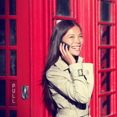 Woman on smart phone by red phone booth — Stock Photo