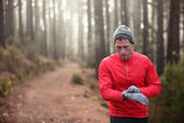 Trail runner looking at heart rate monitor watch — Stock Photo