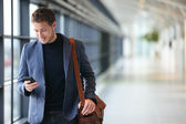 Man on smart phone - business man in airport — Stok fotoğraf