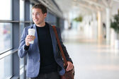 Businessman drinking coffee walking in airport — Stock Photo
