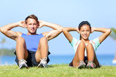 Sit ups - fitness couple exercising sit up outside — Stock Photo