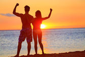 Sporty fitness couple cheering at beach sunset — Stock Photo