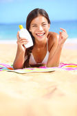 Sunscreen woman showing suntan lotion bottle — Stok fotoğraf