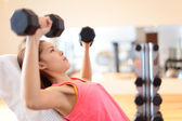 Gym woman strength training lifting weights — Stock Photo