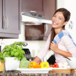 Woman in kitchen making food happy — ストック写真
