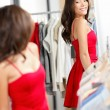 Woman shopping looking in mirror trying clothes dress — Stock Photo
