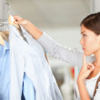 Shopper choosing clothes thinking — Stock Photo #21564391