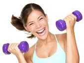 Happy fitness woman lifting dumbbells — Stock Photo