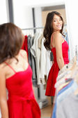 Woman shopping looking in mirror trying clothes dress — Foto Stock