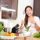 Woman making salad in kitchen — Stock Photo