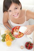 Woman eating breakfast in bed — Stock Photo