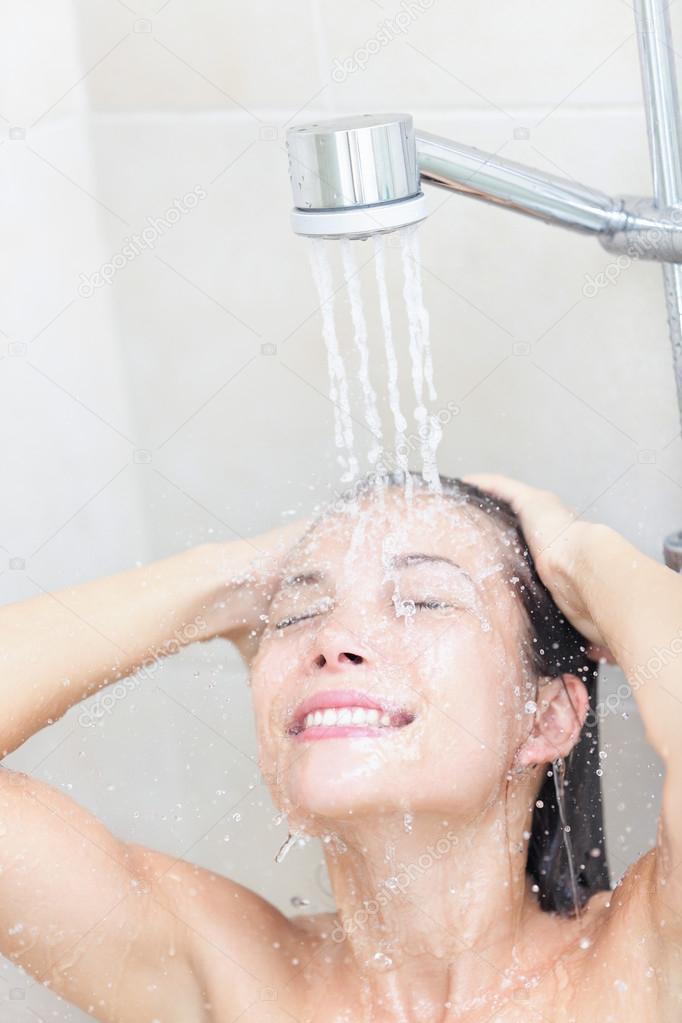 Shower woman washing face and hair smiling happy showering under shower head. Beautiful young joyful mixed race female model in bathroom at home. — Stock Photo #21565361