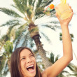 Happy woman with drink at tropical resort toasting — Stock Photo #22926440