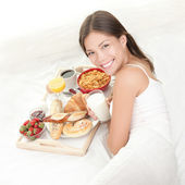 Breakfast woman eating in bed — Stock Photo