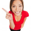Grinning woman pointing to left of frame — Stock Photo