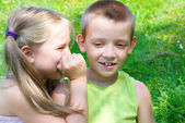 Little girl whispering something to her brother — Stock Photo