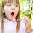 Stock Photo: Little girl blowing soap bubbles
