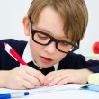 Schoolboy writing homework in workbook — Stock Photo