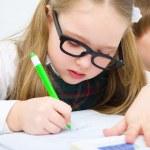 Little schoolchildren writing in workbook — Stock Photo