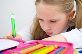 Little schoolgirl writing homework — Stock Photo