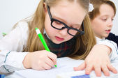 Little schoolchildren writing in workbook — Stock Photo