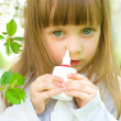 Stock Photo: Girl spraying medicine in nose.