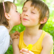 Young girl gives her brother a kiss on the cheek — Stock Photo #24925667