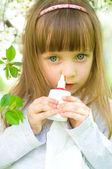 Girl spraying medicine in nose. — Stock Photo