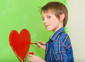 Boy drawing red heart — Stock Photo