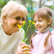 Girl giving her great grandmother flowers — Foto Stock