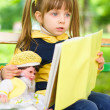 Pretty young girl reads a book with her doll — Stock Photo #26259895