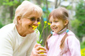 Girl giving her great grandmother flowers — Stock Photo
