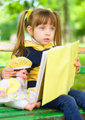 Pretty young girl reads a book with her doll — Stock Photo