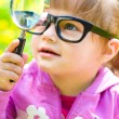 Foto de Stock  : Child playing with magnifying glass