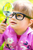 Child playing with magnifying glass — Stock Photo