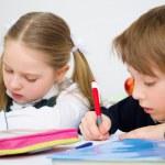 Schoolchildren writing in workbook — Stock Photo #30037461