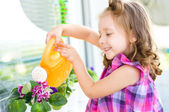 Child watering flowers — Stock Photo