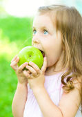 Child is biting green apple — Stock Photo