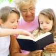 Grandmother reading a book for grandchildren — Stock Photo
