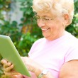 Stock Photo: Elderly womworking on tablet