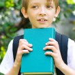 Schoolboy with backpack and book — Stock Photo