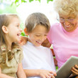 Grandmother with grandchildren using tablet PC — Stock Photo