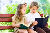 Portrait of cute kids reading book — Stock Photo