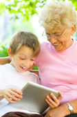 Little boy with grandmother using tablet PC — Stock Photo