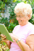 Elderly woman working on a tablet — Stock Photo