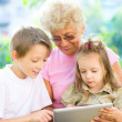 Grandmother with grandchildren using tablet — Stock Photo #30732371