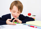 Schoolboy writing homework — Stock Photo