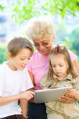 Grandmother with grandchildren using tablet — Stock Photo