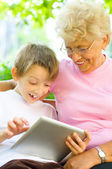 Boy with his grandmother using tablet — Stock Photo