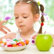 Stock Photo: Child choosing between apple and sweets